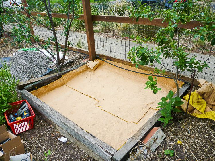 Step 1 carpet underlay to protect the black plastic from the soil below (stones).