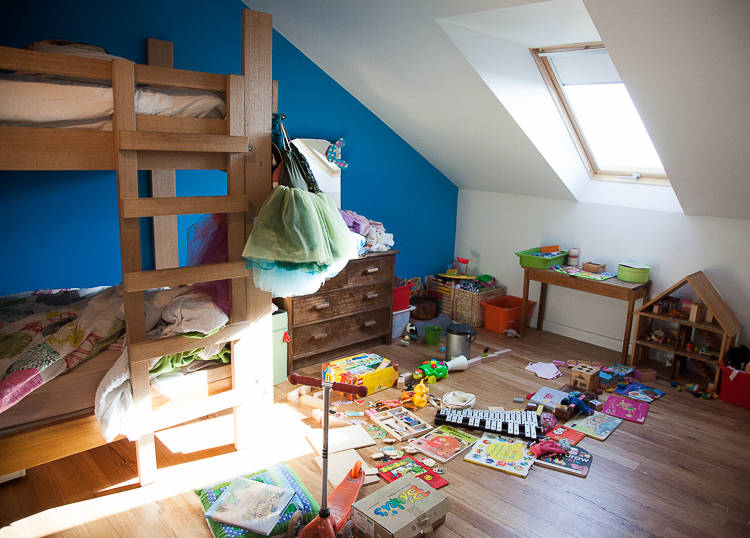 A room with a bed and too many toys, one lonely set of draws with more to be made.